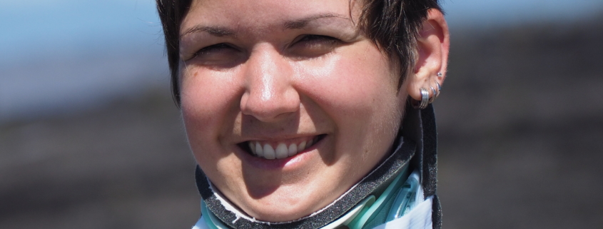 Karina, a woman with short brown hair is smiling, her eyes small from the sun in her face. She is wearing a neck brace and her flower tattoo on her shoulder is visible