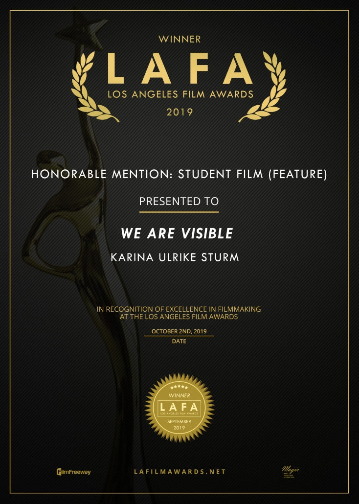 Gewinnerurkunde mit goldenem Text auf schwarzem Untergrund. Im Hintergrund ist eine goldene Statue zu sehen. Text: Winner, LAFA, Los Angeles Film Awards 2019, Honorable Mention: Student Film We Are Visible, Karina Ulrike Sturm.