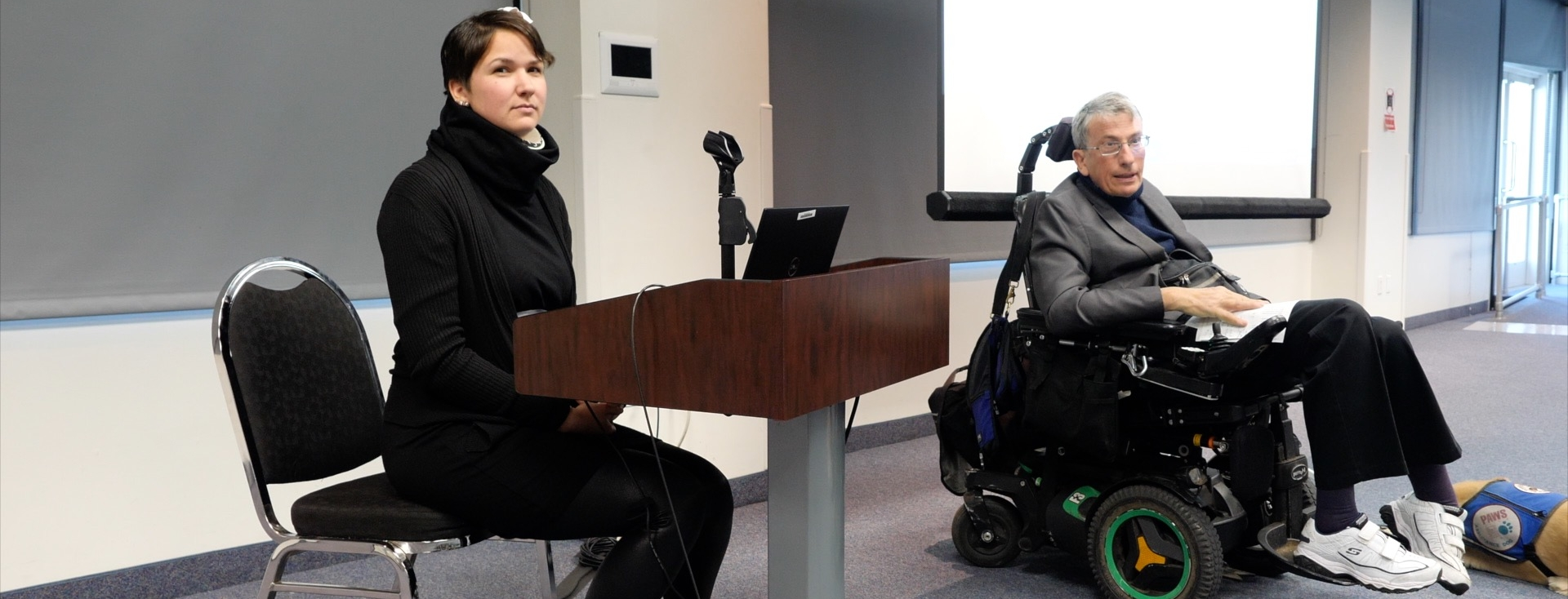 Karina, who has short brown hair sits at a podium listening to the audience. Next to her is a man with glasses in a wheelchair with a service dog next to him.