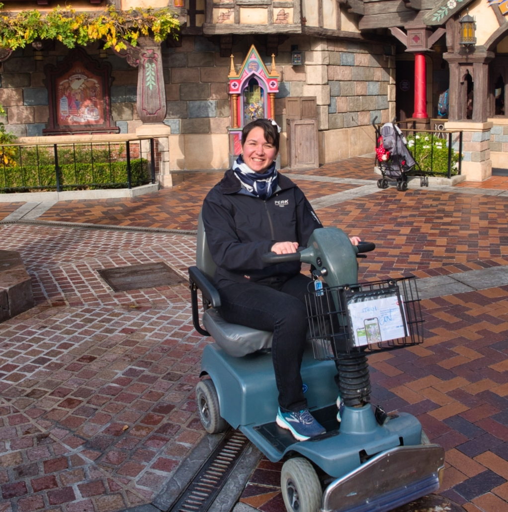 Karina, a woman with short brown hair sits in an e-scooter in front of a Disney castle