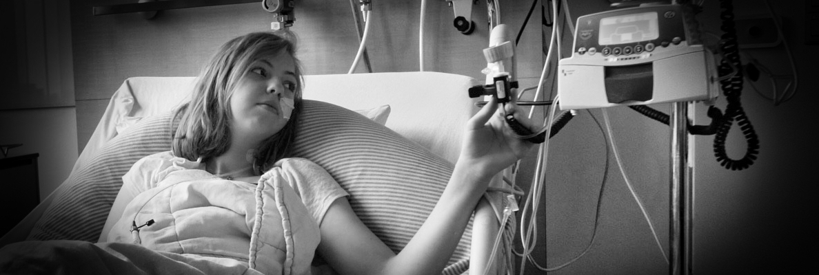 A black and white photo of Jade, a young girl with shoulder-long hair in a hospital bed. He has a tube up her nose and holds an IV in her hand.