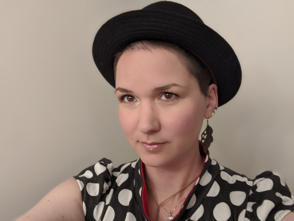 Karina, a woman with super short brown hair and a black hat. She wears a polka dot shirt and feather-like earrings
