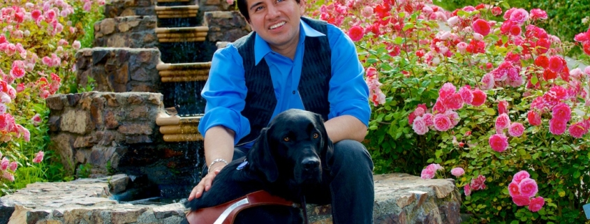 Belo, a young man with short brown hair sits on beautiful stairs in a garden covered in red roses. He smiles and has one hand on his black guide dog