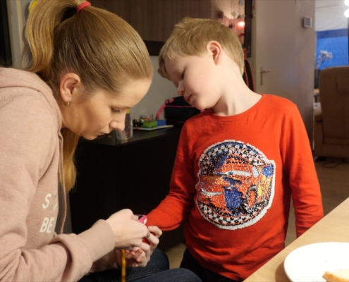 A woman with long blonde hair is measuring oxygen levels of a young boy with blonde hair