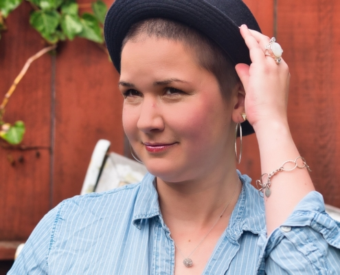Karina, a woman with short brown hair is wearing a black hat and huge earrings
