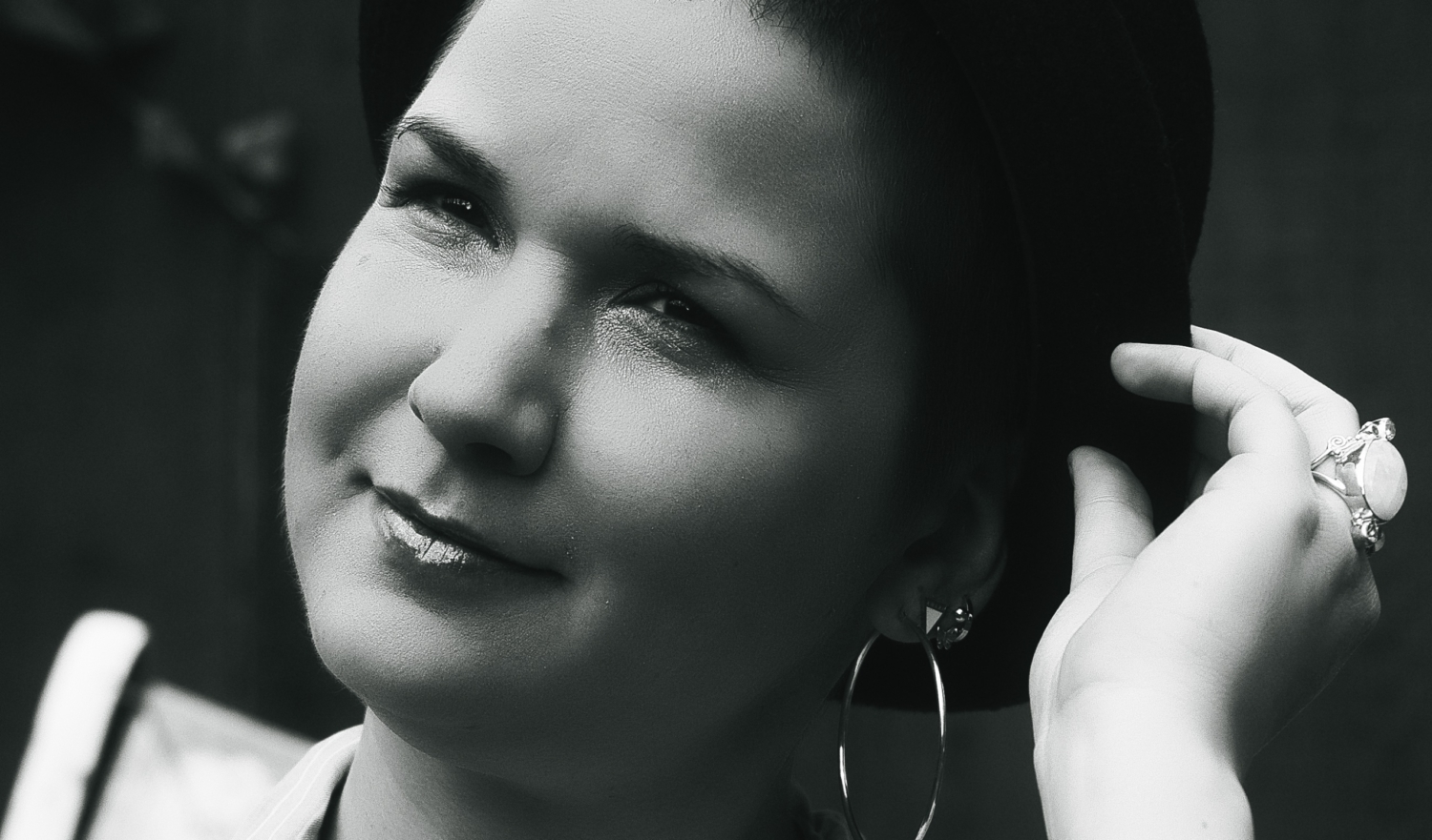 Black and white shot of karina, a woman with super short brown hair, wearing a hat and huge hoop earrings