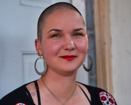 Karina, a woman with super short, shaved hair sits in front of a door. She is wearing red lipstick and large silver hoop earrings