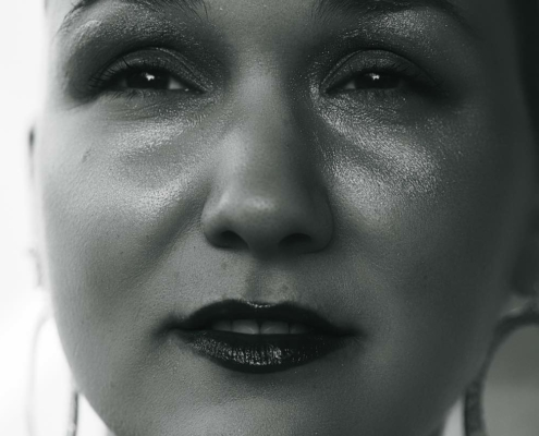 Black and white image of Karina, a woman with shaved head. She is wearing glitter eye shadow and red lipstick.