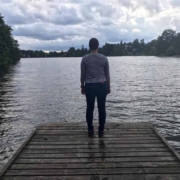 A woman stands on a wooden walkway of a lake and looks into the distance with a threatening dark and cloudy sky above